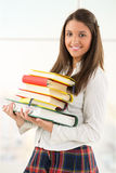 Lycklig kvinnlig student med böcker arkivbild