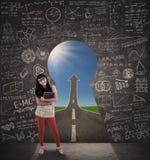 Lycklig kvinnlig student- och framgångvägsikt från nyckelhålet Arkivfoton