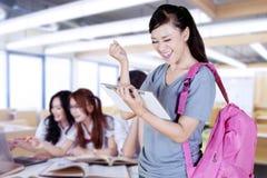 Lycklig kvinnlig student som firar hennes framgång arkivbild