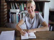 Lycklig kvinnlig student som gör läxa arkivfilmer