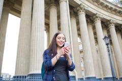 Lycklig kvinnlig student som har den videopd appellen på celltelefonen, stående det fria mot universitet arkivbild