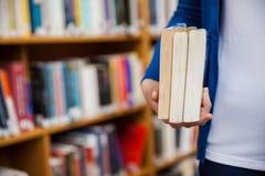 Lycklig kvinnlig student som tar böcker i arkivet royaltyfri bild