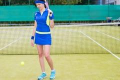 Lycklig kvinnlig tennisspelare som rymmer en racket på hennes skuldrathro Royaltyfri Foto