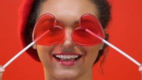 Lycklig kvinnlig tonåring i den stilfulla röda basker som rymmer hjärtagodisframdelen av ögon stock video