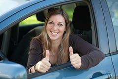 Lycklig kvinnligchaufför som visar upp tum Arkivfoton