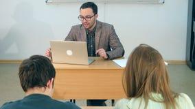 Lycklig lärare med bärbara datorn som ger kurs till en grupp royaltyfri foto