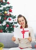 Lycklig läs- julvykort för ung kvinna nära julträd Royaltyfri Foto