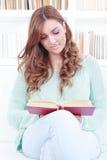 Lycklig läs- sagobok för ung kvinna på soffan hemma royaltyfria bilder