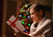 Lycklig läs- vykort för ung kvinna framme av julträdet Royaltyfri Foto