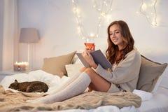 Lycklig läsebok för ung kvinna i säng hemma arkivfoto