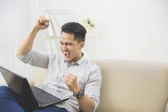 lycklig lönelyft för ung man hans hand framgång arkivfoto