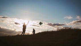 Lycklig lansering för familjfader- och barndotter en drake på äng på solnedgången Rolig familjtid Begrepp av den vänliga familjen stock video