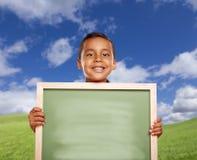 Lycklig latinamerikansk pojke i bräde för krita för mellanrum för innehav för gräsfält Royaltyfria Foton