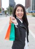 Lycklig latinsk kvinna med två shoppingpåsar Fotografering för Bildbyråer