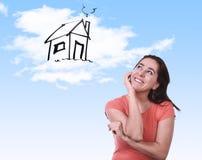 Lycklig latinsk kvinna som drömmer av fastighetbegrepp för nytt hus royaltyfri foto