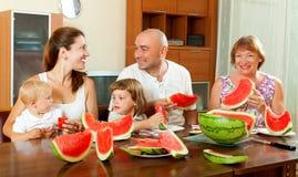 Lycklig laughting familj som har vattenmelon bak tabellen Royaltyfri Foto