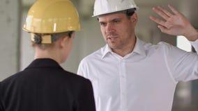 Lycklig le affärsman och affärskvinna som talar, medan arbeta på konstruktionsplatsen lager videofilmer