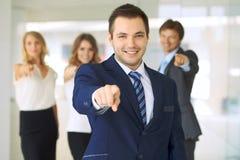 Lycklig le affärsman och hans kollegor som pekar vid fingret in i kameran Begrepp av arbetsgivaren och framgånglaget royaltyfri fotografi