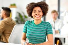 Lycklig le afrikansk amerikankvinna på kontoret royaltyfri foto