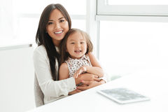 Lycklig le asiatisk mamma som rymmer hennes lilla dotter fotografering för bildbyråer