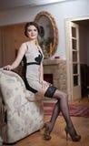 Lycklig le attraktiv kvinna som bär en elegant klänning och svarta strumpor som sitter på soffaarmen Härlig ung sinnlig flicka Royaltyfri Bild