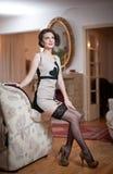 Lycklig le attraktiv kvinna som bär en elegant klänning och svarta strumpor som sitter på soffaarmen Härlig ung sinnlig flicka Arkivbilder