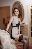 Lycklig le attraktiv kvinna som bär en elegant klänning och svarta strumpor som sitter på soffaarmen Härlig ung sinnlig flicka Royaltyfri Fotografi