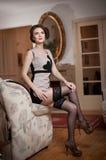 Lycklig le attraktiv kvinna som bär en elegant klänning och svarta strumpor som sitter på soffaarmen Härlig ung sinnlig flicka Arkivbild
