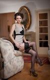 Lycklig le attraktiv kvinna som bär en elegant klänning och svarta strumpor som sitter på soffaarmen Härlig ung sinnlig flicka Royaltyfria Bilder
