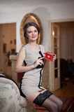 Lycklig le attraktiv kvinna som bär en elegant klänning och svarta strumpor som sitter på soffaarminnehavet en liten röd ask Royaltyfria Bilder