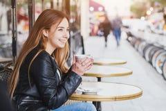 Lycklig le attraktiv ung kvinna med koppen kaffe i gatakafé arkivfoton