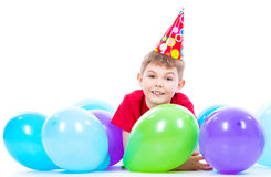 Lycklig le boylying på golvet med färgrika ballonger Royaltyfria Bilder