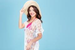Lycklig le brunett i bikinin som poserar på blå bakgrund Fotografering för Bildbyråer