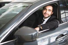 Lycklig le chaufför i bilen, stående av den unga lyckade affärsmannen arkivfoto