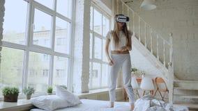 Lycklig le dans för ung kvinna, medan få erfarenhet genom att använda 360 VR-hörlurar med mikrofonexponeringsglas av virtuell ver lager videofilmer