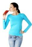 Lycklig le dricka tomatfruktsaft för kvinna Arkivfoto