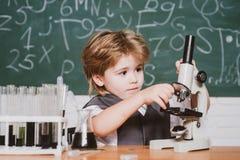 Lycklig le elevteckning p? skrivbordet schoolchild Det var lite kemiexperimentet Kemikurs skola arkivfoton
