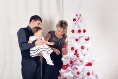 Lycklig le familj nära julgranen arkivbilder