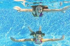 Lycklig le familj som är undervattens- i simbassäng Arkivfoton