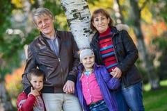 Lycklig le familjstående för fyra personer utomhus Arkivbilder