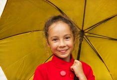 lycklig le flicka i ett rött omslag som rymmer ett gult paraply royaltyfri bild