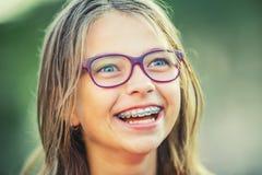Lycklig le flicka med tand- hänglsen och exponeringsglas Bärande tandhänglsen och exponeringsglas för ung gullig caucasian blond  royaltyfria foton