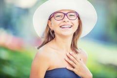 Lycklig le flicka med tand- hänglsen och exponeringsglas Bärande tandhänglsen och exponeringsglas för ung gullig caucasian blond  arkivfoto