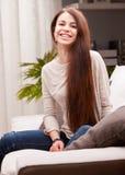 Lycklig le flicka på en soffa Arkivfoto
