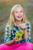 Lycklig le flicka som äter utomhus- sunda druvor Arkivfoton