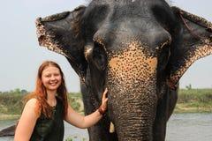 Lycklig le flickahandelsresande med rött hår i en grön t-skjorta som rymmer en stor elefant royaltyfri bild