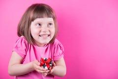 Lycklig le gullig liten flicka som rymmer den nätta prickiga gåvaasken i hennes händer på ljus rosa bakgrund Fotografering för Bildbyråer