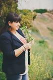 Lycklig le härlig överviktig ung kvinna i mörker - blått omslag utomhus med blommor Säker fet ung kvinna Xxl kvinna Arkivfoton