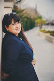 Lycklig le härlig överviktig ung kvinna i mörker - blått omslag utomhus på gatan Säker fet ung kvinna Xxl kvinna Arkivfoton
