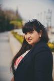 Lycklig le härlig överviktig ung kvinna i mörker - blått omslag utomhus på gatan Säker fet ung kvinna Xxl kvinna Arkivfoto